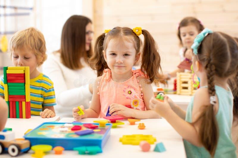 Vorschulkinderspiel mit bunten didaktischen Spielwaren am Kindergarten stockfotos
