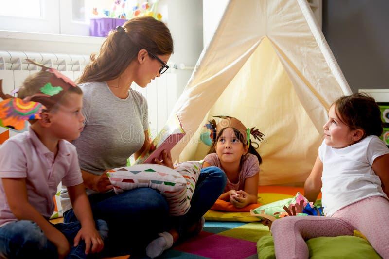 Vorschullehrer, der eine Geschichte zu den Kindern am Kindergarten liest lizenzfreie stockfotos
