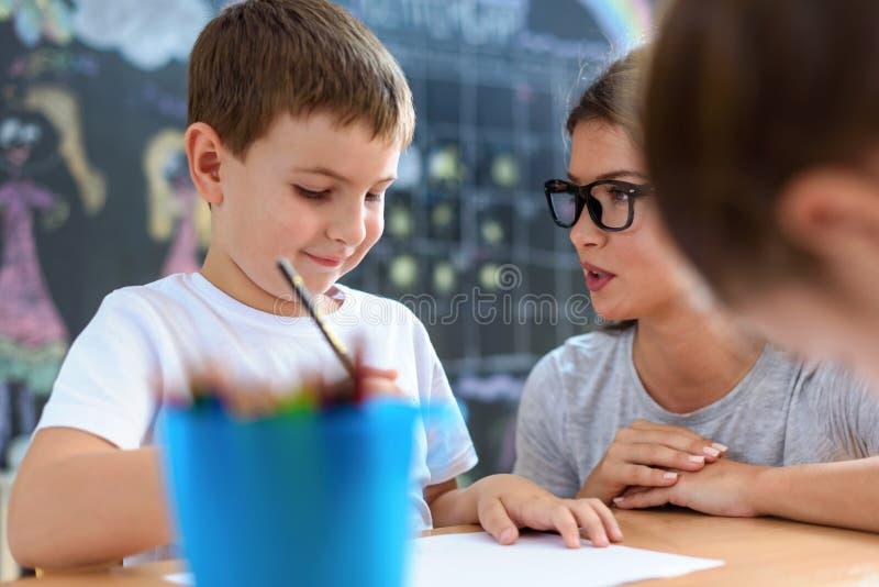 Vorschullehrer, der intelligentes Kind auf Kindergarten betrachtet stockbild