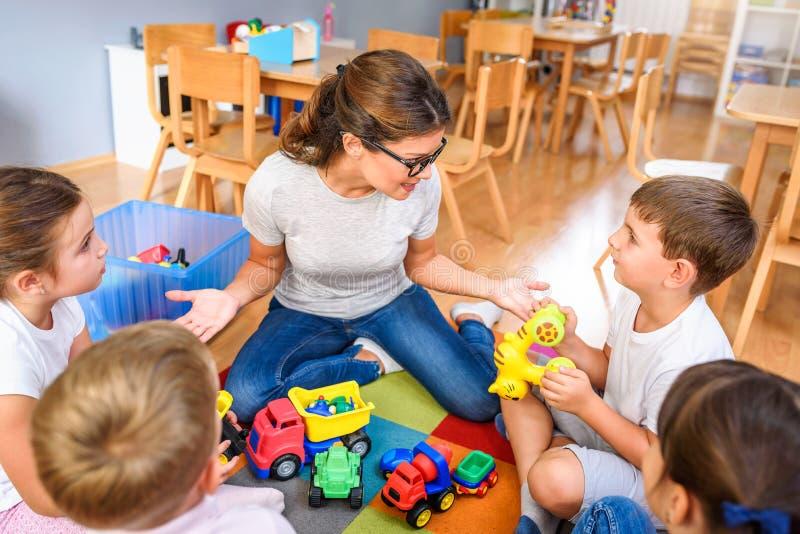 Vorschullehrer, der mit Gruppe Kindern sitzen auf einem Boden am Kindergarten spricht lizenzfreie stockfotografie