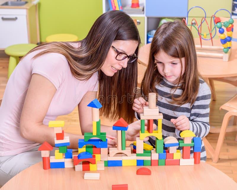 Vorschullehrer Instructs Cute Girl, wie man Toy Castle errichtet stockfoto