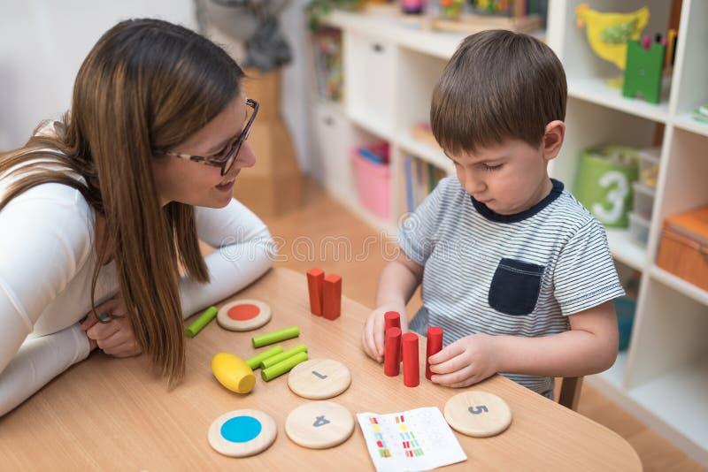 Vorschullehrer mit dem Kind, das kreative pädagogische Tätigkeiten hat stockfotos