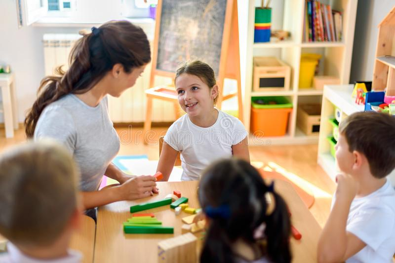 Vorschullehrer mit den Kindern, die mit bunten didaktischen Spielwaren am Kindergarten spielen lizenzfreie stockbilder