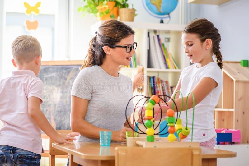 Vorschullehrer mit den Kindern, die mit bunten didaktischen Spielwaren am Kindergarten spielen stockfoto