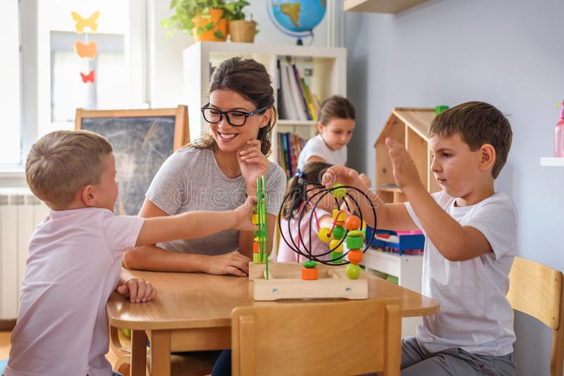 Vorschullehrer mit den Kindern, die mit bunten didaktischen Spielwaren am Kindergarten spielen stockbild