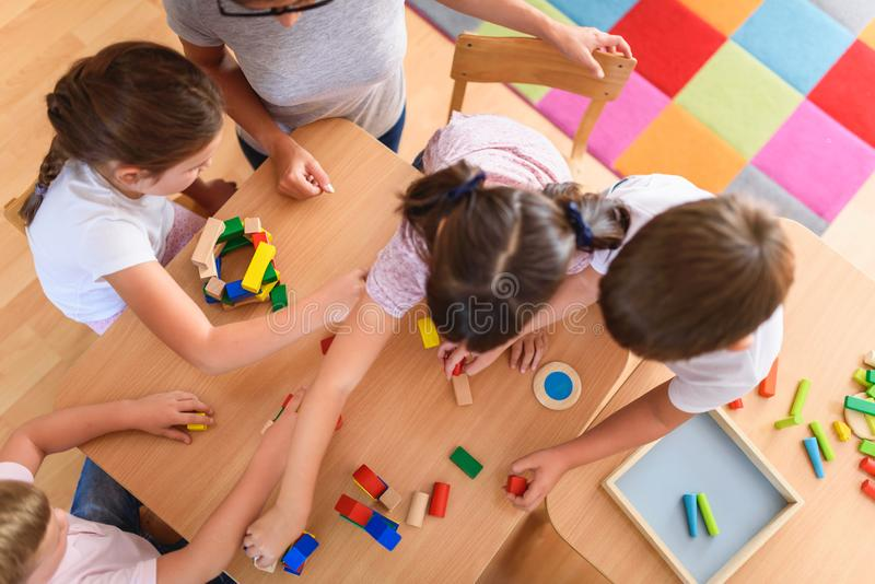 Vorschullehrer mit den Kindern, die mit bunten hölzernen didaktischen Spielwaren am Kindergarten spielen stockfoto