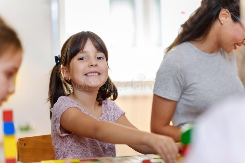 Vorschullehrer mit den Kindern, die mit bunten hölzernen didaktischen Spielwaren am Kindergarten spielen lizenzfreies stockbild