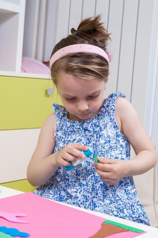 Vorschulmädchengebrauchskleber für Hausarbeit vom Kindergarten lizenzfreie stockbilder