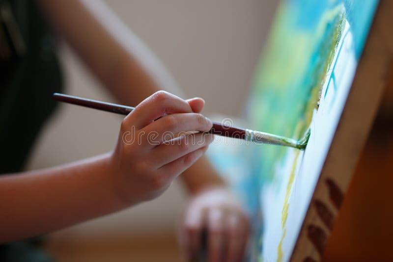 Vorschulmädchenmalerei im Kunstunterricht Schließen Sie herauf Fotobürste in der Hand lizenzfreie stockfotos