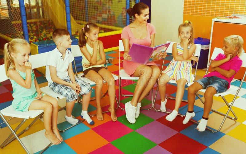 Vorsichtige Kinder, die mit Lehrer sitzen und auf Buch hören lizenzfreies stockbild