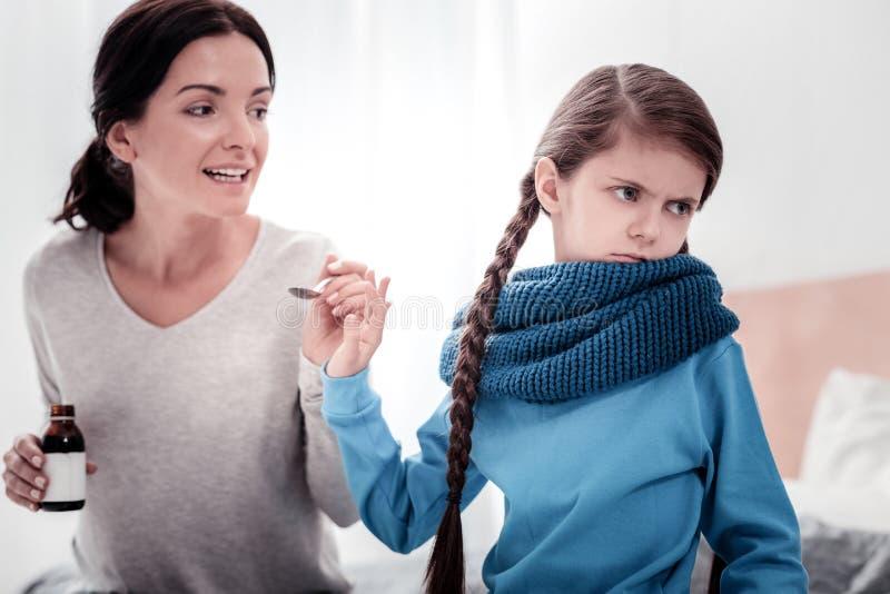 Vorsichtige Mutter mit Hustensirup und ungehorsam sein Kind stockbilder