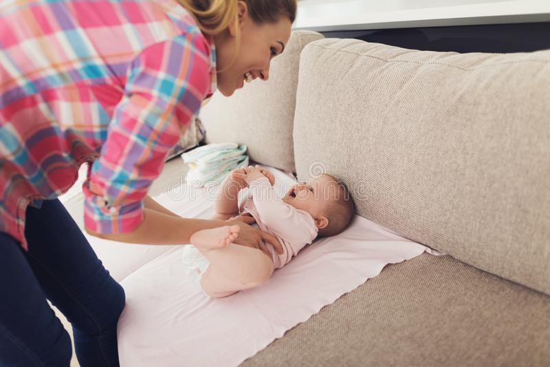Vorsichtige Mutter wickelt lächelndes Baby auf Couch lizenzfreies stockbild