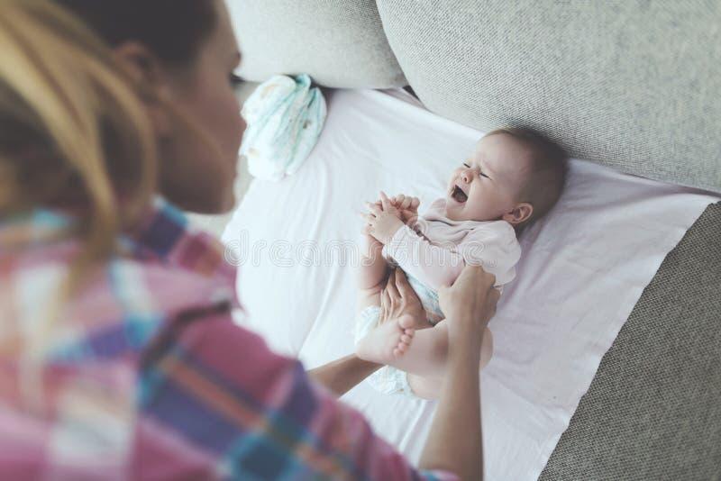 Vorsichtige Mutter wickelt schreiendes Baby auf Couch stockfoto