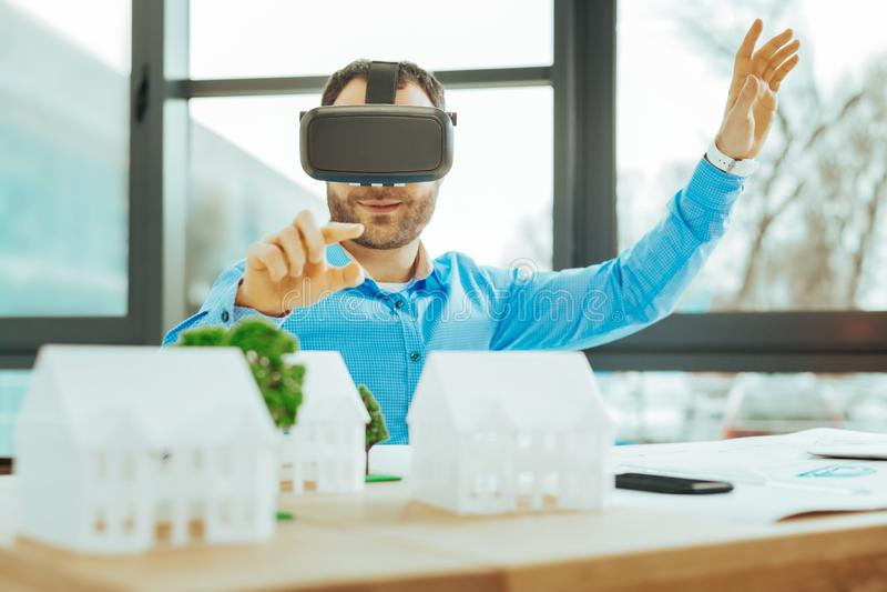 Vorsichtiger Ingenieur unter Verwendung der virtuellen Realität beim Arbeiten mit Miniaturen lizenzfreie stockbilder