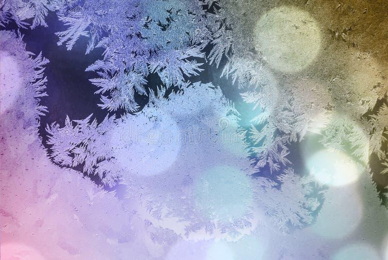 Vorst op venster Glans door glas Feestelijke achtergrond met de winterthema bokeh vage abstracte kleurrijke achtergrond stock foto