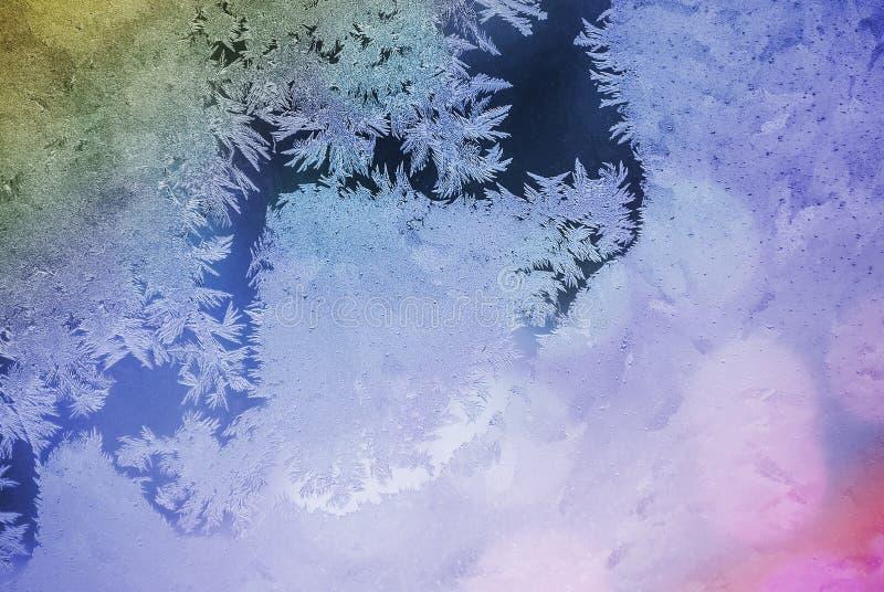 Vorst op venster Glans door glas Feestelijke achtergrond met de winterthema bokeh vage abstracte kleurrijke achtergrond royalty-vrije stock fotografie