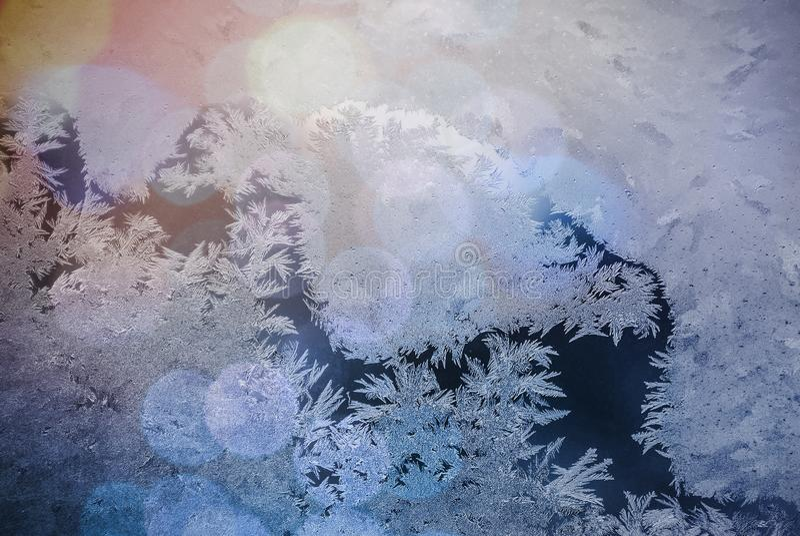 Vorst op venster Glans door glas Feestelijke achtergrond met de winterthema bokeh vage abstracte kleurrijke achtergrond royalty-vrije stock afbeeldingen