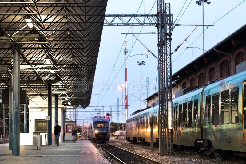 Vorstadtzug, welche der Plattform Larissa Train Stas sich nähert stockfotografie