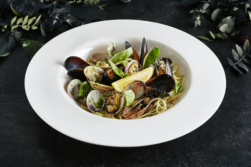 Vorzügliche dienende weiße Restaurant-Platte von Spaghettis Nido mit Seeoberteilen in der Wein-Soße lizenzfreie stockbilder