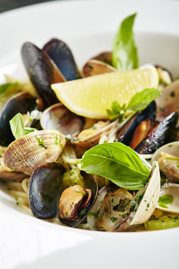 Vorzügliche dienende weiße Restaurant-Platte von Spaghettis Nido mit Seeoberteilen in der Wein-Soße stockbild