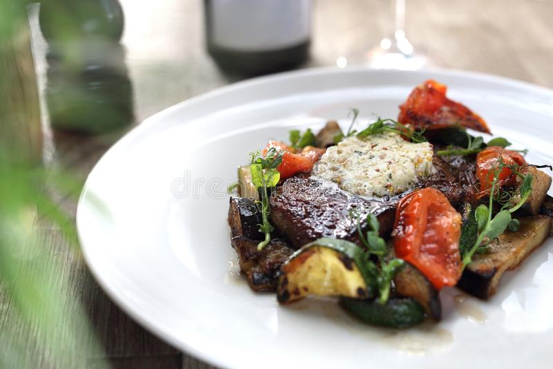 Vorzügliches, elegantes Abendessen Rindfleischsteak mit Kräuterbutter und gegrilltem Gemüse lizenzfreie stockfotografie