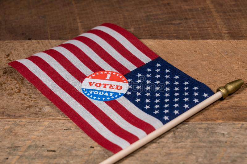 Voté hoy la etiqueta engomada de papel en bandera de los E.E.U.U. y la tabla de madera rural imagen de archivo libre de regalías