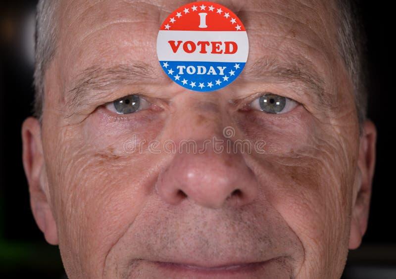 Voté la etiqueta engomada de papel encendido sirvo hoy la frente con sonrisa caliente en la cámara fotografía de archivo