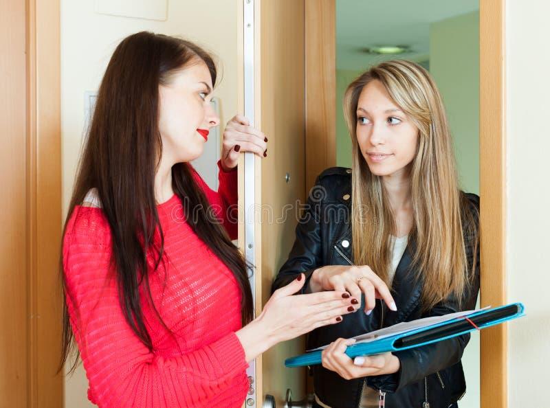 Votação fêmea nova do empregado entre a porta dos povos em casa fotos de stock royalty free