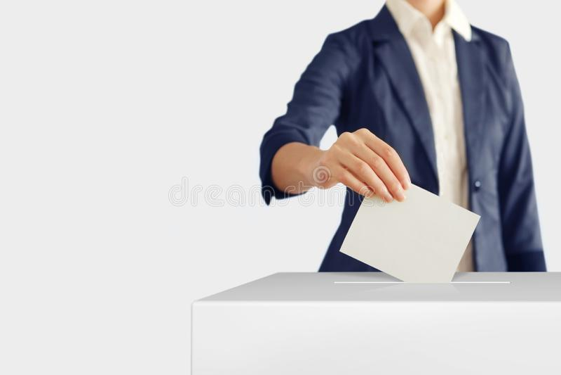 votaci?n Mujer que pone una votaci?n en una caja de votaci?n fotos de archivo libres de regalías
