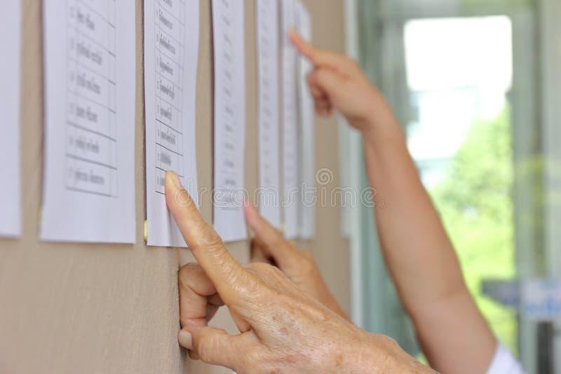 Votantes elegibles que comprueban para saber si hay su nombre en la cabina de votar antes de la elección, con nombre borroso fotos de archivo