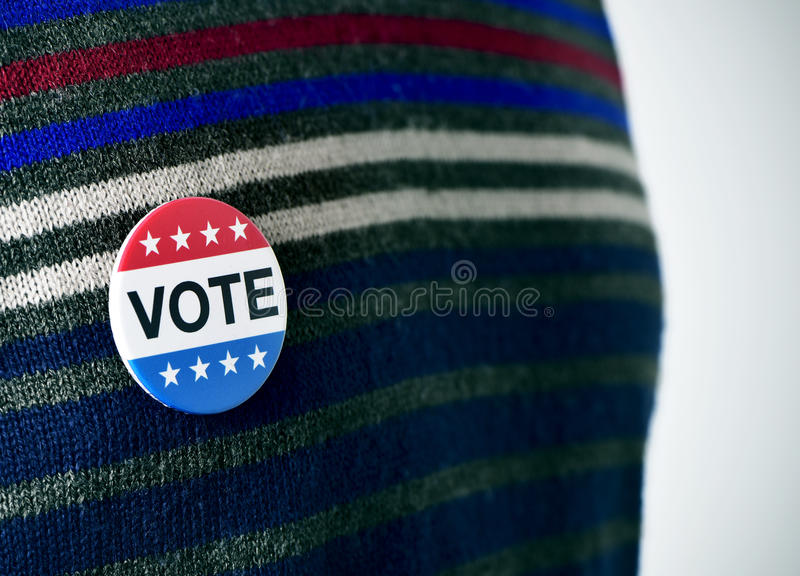 Vote badge for the United States election. Closeup of a vote badge for the United States election pinned in the sweater of a young man royalty free stock photo