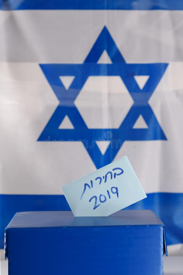 Vote box. Hebrew text Elections 2019 on voting paper over Israel flag background. stock photography