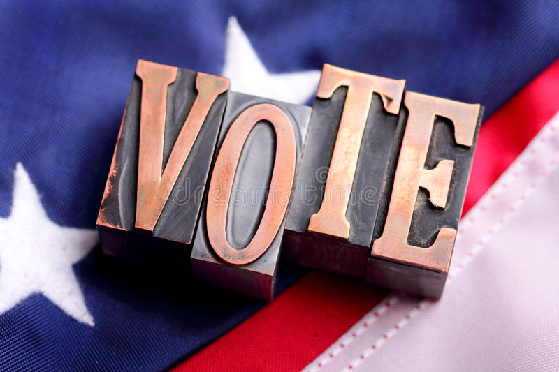 VOTE letters on American Flag. Letterpress blocks forming word VOTE letters on Stars and Stripes American flag background. shallow depth of field stock images