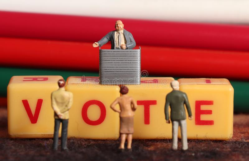 Vote. Spelled on yellow blocks with miniature people stock photography