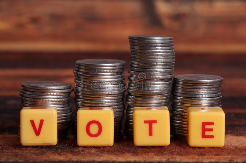 Vote. Spelled on yellow blocks with pile of money stock image