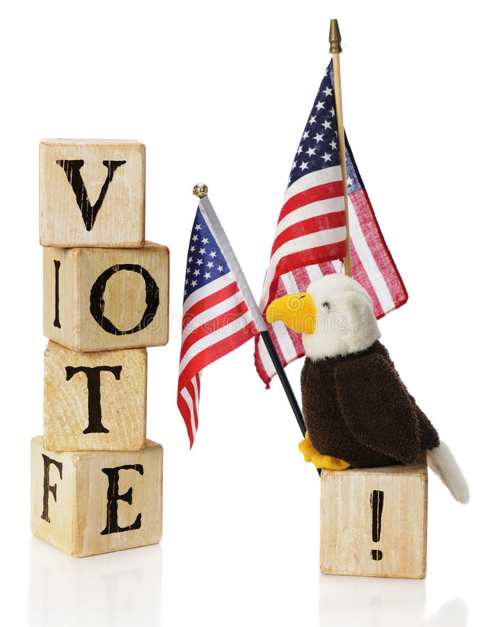 Vote, USA. A toy bald eagle looking at the word VOTE constructed of rustic alphabet block, while he's perched on an exclaimation point by two US flags. On a stock photos
