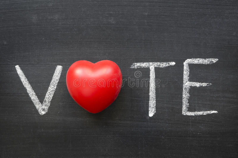 Vote. Word handwritten on blackboard with heart symbol instead O royalty free stock photo