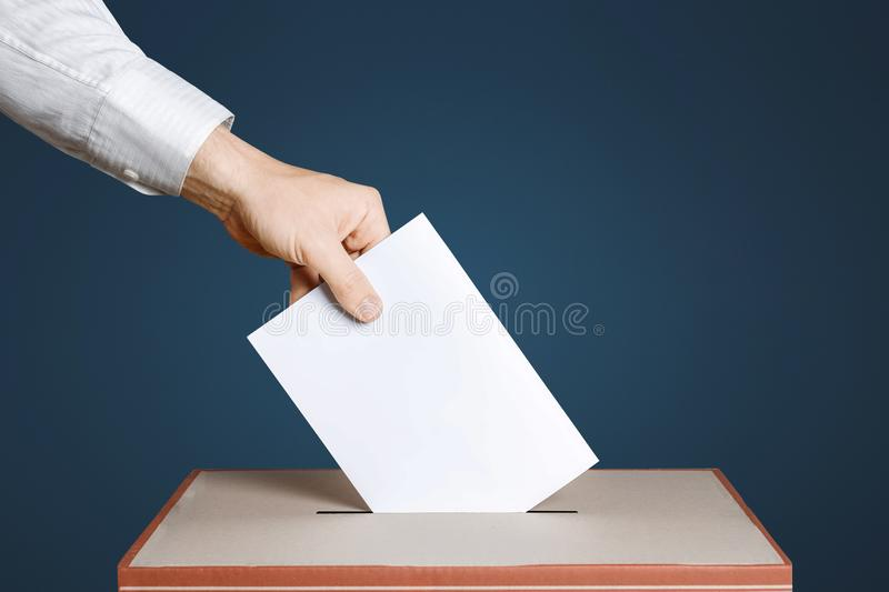 Voter Holds Envelope In Hand Above Vote Ballot. Blue background. Democracy Concept. Voter hand puts the ballot into the ballot box. The concept of democracy and stock photo