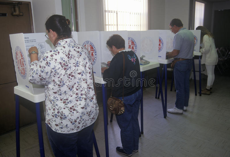 Voters and voting booths in a polling place. CA royalty free stock image