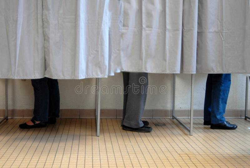 Voters voting in polling booths. Privacy concept with people voting in booths stock photos