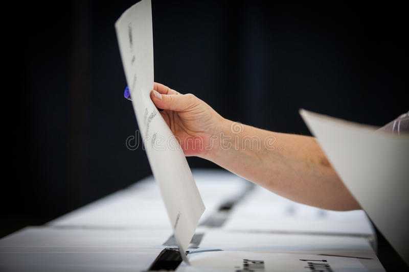 Voting hand detail. Hand of a person casting a ballot at a polling station during voting royalty free stock photography