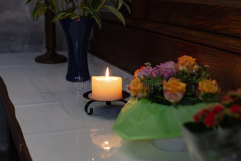 votive Altar in der Kirche mit den grünen und rosa Blumen stockfotos