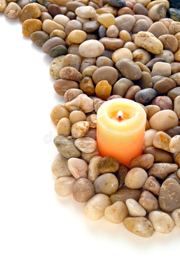 Votive Candle Burning in Bed of Pebbles over White royalty free stock photo