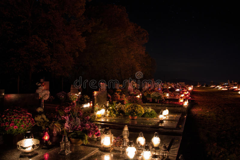 Votive candles lantern burning on the graves in Slovak cemetery at night time. All Saints' Day. Solemnity of All Saints. All Hallows eve. 1st November. Feast royalty free stock image