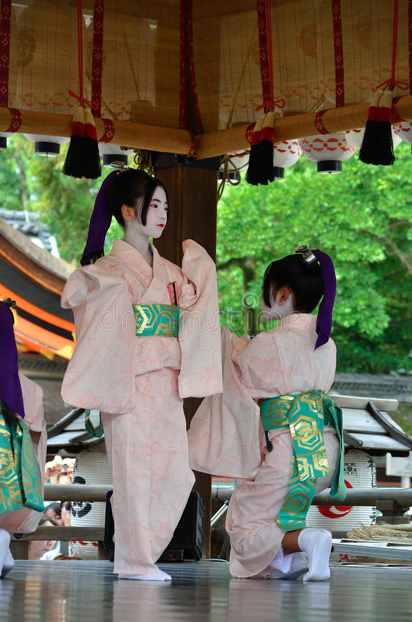 Votive dance by Maiko girls, Gion festival scene. Little Maiko girls dedicate their dancing for the holiness of Yasaka Shrine, on the festival day of Gion royalty free stock image