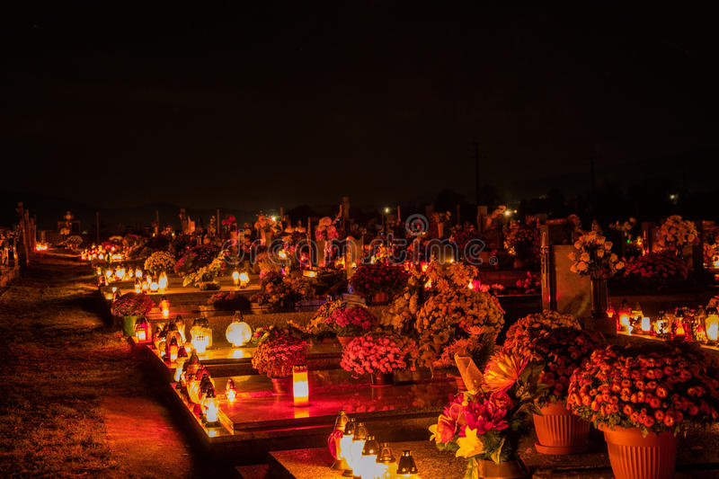 Votive stearinljus lyktabränning på gravarna i slovakisk kyrkogård på nattetid All Saints& x27; Dag Helgon för högtidlighet allra royaltyfria bilder