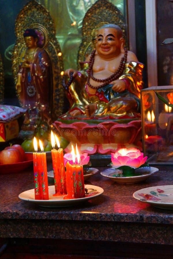Votive stearinljus och rökelse, med Buddha arkivbilder