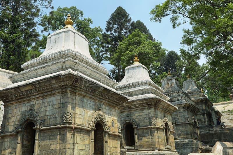 Votive temples in Pashupatinath Temple, Nepal. KATHMANDU, NEPAL - APRIL 20, 2016: Votive temples and shrines in a row at Pashupatinath Temple, Kathmandu, Nepal stock photos