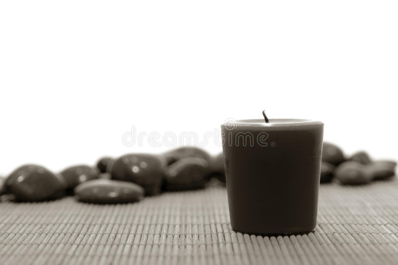 Votive Wax Candle and Pebbles in Spa. Votive wax candle on bamboo mat with stones in a spa stock images