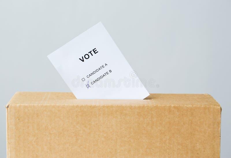 Voto introduzido no entalhe da urna de voto na eleição imagem de stock